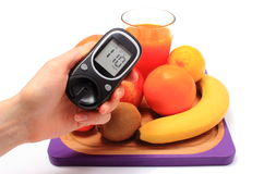 Hand with glucometer, fresh natural fruits, glass of juice Stock Image