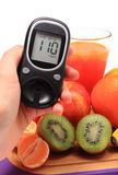 Hand with glucometer, fresh natural fruits, glass of juice Stock Photo