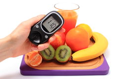 Hand with glucometer, fresh natural fruits, glass of juice Stock Photos