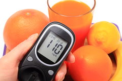 Hand with glucose meter, fresh natural fruits, glass of juice Stock Photos