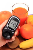 Hand with glucose meter, fresh natural fruits, glass of juice Royalty Free Stock Photography