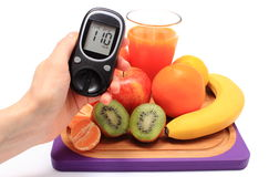 Hand with glucose meter, fresh natural fruits, glass of juice Royalty Free Stock Photo