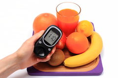 Hand with glucose meter, fresh natural fruits, glass of juice Stock Images