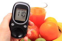 Hand with glucose meter, fresh natural fruits, glass of juice Stock Photo