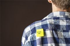 Hand glue yellow kick me sticker on persons back at aprill fool day b royalty free stock image