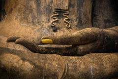 Hand of God. Closeup of the hand of Lord Buddha with gold leaf applied on finger nail stock images