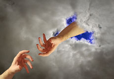 Hand of god help. Conceptual photo of hand of god reaching from heaven to hand of mankind on earth stock photos