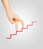 Hand goes on to draw a red ladder Stock Image