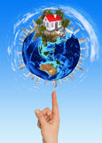 Hand goes to the planet Earth. Blue sky on background Stock Images