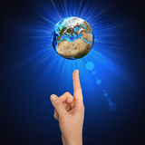 Hand goes to the planet Earth Stock Photography