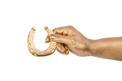 Hand with gold horseshoe Stock Images