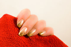 Hand with gold nails holding a red towel Royalty Free Stock Photo