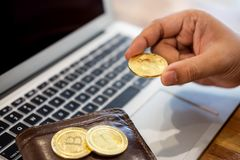 Hand with golden metal Bitcoin crypto currency investment- symbolic block chain financial internet and technology. Hand with golden metal Bitcoin crypto currency royalty free stock photos