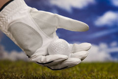 Hand and golf ball Stock Images