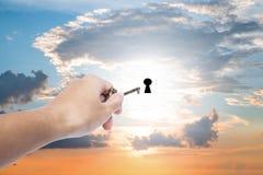 Hand gouden sleutel houden die zich uitbreidt om op zonsonderganghemel, bedrijfs abstract concept te openen Stock Foto's