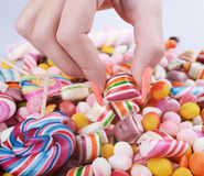 Hand grabbing candy from pile - Overweight problem concept Royalty Free Stock Images