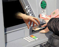 Hand grabbing cash machine. Conceptual photo of a hand coming from screen of cash machine ready to grab hold of customer's cash Royalty Free Stock Photography