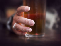 Hand grabbing glass of beer Royalty Free Stock Photos