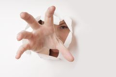 Hand grabbing through hole. Woman grabbing with hand through hole in paper wall Royalty Free Stock Photography