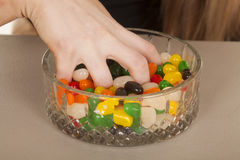 Hand grabbing jelly beans from bowl close Stock Photos
