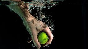 Hand grabbing lime from water Royalty Free Stock Image