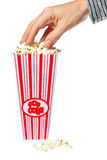 Hand grabbing popcorn out of container Royalty Free Stock Photography