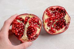 Hand Grabbing a Sliced Pomegranate. A pomegranate sliced in half, being picked up by a hand off-frame royalty free stock photos