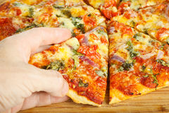 Hand grabbing slize of pizza Royalty Free Stock Photos