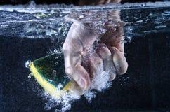 Hand Grabbing Sponge Underwater. Underwater shot of a hand grabbing a soapy sponge Royalty Free Stock Photos