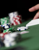 Poker Table Chips. A hand grabs some card in the background of a poker table. gambling chips Royalty Free Stock Photos