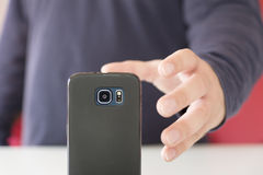 Hand grasping a smartphone. Male hand reaching for a black smartphone Stock Photos