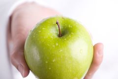 Hand with green apple Royalty Free Stock Images