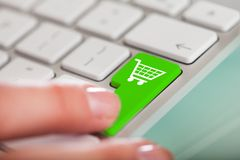 Hand On Green Shopping Cart Button Royalty Free Stock Photo