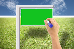 Hand and green sign on the lawn and blue sky. Stock Photos