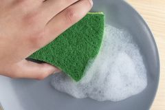 A hand with a green spunge washes a gray ceramic plate with detergent foam royalty free stock photos