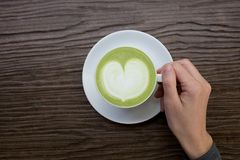 Hand with green tea latte on wood background. Hand with a cup of green tea latte on wood table as a background Stock Photo