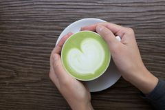 Hand with green tea latte on wood background. Woman hands and with green tea latte on wood background Royalty Free Stock Photos