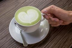 Hand with green tea latte on wood background. Woman hands with a cup of green tea latte on wood background Royalty Free Stock Photo