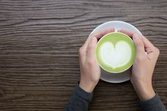Hand with green tea latte on wood background. Woman hands holding cup of green tea latte on wood background Royalty Free Stock Photo