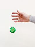 Hand with a green yo-yo. Male hand letting go of a green yo-yo with a smiling frog Stock Image