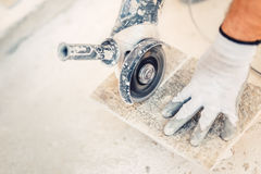 Hand grinder cutting granite stone used for paving Royalty Free Stock Images