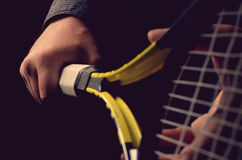 Hand on grip and swinging a tennis racket. Isolated on black background Royalty Free Stock Images