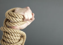Hand gripping rope Stock Photos