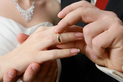 Hand of groom putting a ring on finger of his bride Stock Photo