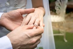Hand of the groom wears a wedding ring bride. /groom wears a wedding ring on the bride`s wedding Stock Photos
