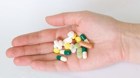 Hand with group of pills and capsules Royalty Free Stock Photos
