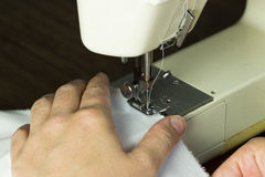 Hand guiding cloth through a sewing machine Royalty Free Stock Photos