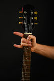 Hand with guitar and devil horns  on black Stock Images