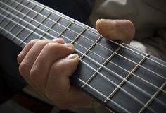 Hand on guitar fingerboard. A closeup view of a hand and fingers on a guitar fingerboard or fretboard Stock Image