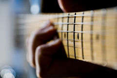 Hand on Guitar Fretboard. Close-up of the fretboard of an electric guitar with a hand out-of-focus in the background Royalty Free Stock Image